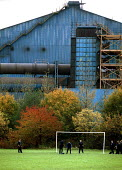 Schoolboys playing football near steelworks Cardiff Comprehensive School South Wales. - John Harris - ,2000s,2001,adolescence,adolescent,adolescents,ASW,autumn,AUTUMNAL,boy,boys,capitalism,Celsa,child,CHILDHOOD,children,EBF economy,EDU education,ENI environmental issues,FACTORIES,factory,field,fields,