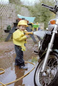 Toddler at 2yrs 10 months playing with garden hose, cleaning a very large capacity Triumph motorcycle. - John Harris - 28-03-2002