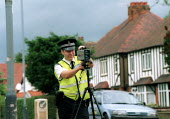 Armed policeman measuring the speed of oncoming vehicles with a handheld laser equiped speed measuring device - John Harris - 2000s,2002,30,adult,adults,armed,arms,AUTO,AUTOMOBILE,AUTOMOBILES,AUTOMOTIVE,beat,bike,bikes,car,cars,checks,CLJ crime law,cop,device,enforcement,Firearm,firearms,fixed,force,gun,guns,handheld,highway