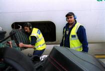 Baggage handlers unloading luggage from airplane at Birmingham International Airport. - John Harris - 2000s,2002,Aeroplane,AEROPLANES,air transport,aircraft,airplane,airplanes,aviance,aviation,bag,Baggage,bags,BAME,BAMEs,Birmingham,Black,BME,bmes,cargo,cities,city,diversity,ear,Ear Protectors,EBF econ