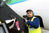 Baggage handlers unloading luggage from airplane at Birmingham International Airport. - John Harris - 2000s,2002,Aeroplane,AEROPLANES,air transport,aircraft,airplane,airplanes,asian,aviance,aviation,bag,Baggage,bags,BAME,BAMEs,Birmingham,black,BME,bmes,cargo,cities,city,diversity,ear,Ear Protectors,EB