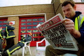 FBU picket reads The Sun newspaper, with a headline - Fire Union chiefs are Saddam Stooges - a story suggesting FBU leaders promoted Saddam Hussein. Firefighters strike picket line. Stratford upon Avo... - John Harris - 2000s,2002,adult,adults,anti union,DISPUTE,DISPUTES,FBU,Fire,fire brigade,Firefighter,Firefighters,Firefighters' strike,fireman,firemen,fires,gutter press,hardline,headline,headlines,INDUSTRIAL DISPUT
