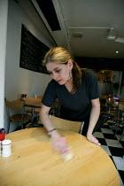 Waitress cleaning a table down. Cafe restaurant Stratford on Avon. - John Harris - 20-05-2003