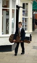 Grammar School pupil walking home from school with his guitar in a guitar case. Stratford on Avon - John Harris - 2000s,2003,6th,adolescence,adolescent,adolescents,boy,boys,child,CHILDHOOD,children,class,EDU education,edward,fed,guitar,Guitarist,Guitarists,home,intelligence,intelligent,juvenile,juveniles,kid,kids