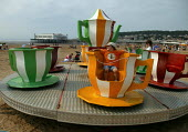 Child riding on a teacup roundabout on the beach Weston Super Mare in the hottest temperatures. - John Harris - 04-08-2003