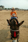 Child riding a donkey on the beach, Weston Super Mare in the hottest temperatures. - John Harris - 2000s,2003,animal,animals,beach,BEACHES,boy,BOYS,castles,child,CHILDHOOD,children,coast,coastal,coasts,Day Trip,Day Tripper,Day Trippers,domesticated ungulate,domesticated ungulates,donkey,donkeys,Emi