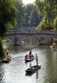 Students and tourists punting along The Backs, by Clare Bridge, Clare College, Cambridge. Punt chauffeurs push them along. - John Harris - 10-08-2003