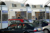 Worker in a Toll Booth as a driver pays. M6 Toll Road is the first tolled motorway in Britain, and is intended to reduce the congestion on the M6. Birmingham Northen Relief Road Weeford Toll booths, W... - John Harris - 09-12-2003