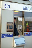 Worker in a Toll Booth. M6 Toll Road is the first tolled motorway in Britain, and is intended to reduce the congestion on the M6. Birmingham Northen Relief Road Weeford Toll booths, West Midlands. - John Harris - 09-12-2003