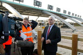 TV crew about to interview the Sec of State for Transport Alistair Darling MP at the opening of the M6 Toll Road. The M6 toll is the first tolled motorway in Britain, and is intended to reduce the con... - John Harris - 2000s,2003,AUTO,AUTOMOBILE,AUTOMOBILES,AUTOMOTIVE,Birmingham,booth,booths,broadcast,broadcasting,camera,cameras,car,cars,charges,cities,city,communicating,communication,CONGESTED,congestion,crew,EBF e