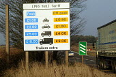 Sign showing tarrif for motorcycles, cars, vans and lorries. M6 Toll Road is the first tolled motorway in Britain, and is intended to reduce the congestion on the M6. Birmingham Northen Relief Road We... - John Harris - 2000s,2003,AUTO,AUTOMOBILE,AUTOMOBILES,AUTOMOTIVE,Birmingham,booth,booths,CAR,cars,charges,communicating,communication,CONGESTED,congestion,EARNINGS,EBF economy,fee,highway,infrastructure,job,jobs,LAB