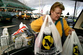 Shopper loading the car at Morrisons Supermarket. - John Harris - 2000s,2004,bag,bags,bought,buy,buyer,buyers,buying,commodities,commodity,consumer,consumers,customer,customers,EBF economy,FEMALE,filling,food,FOODS,goods,groceries,LFL,LIFE,loading,Morrisons,outlet,o