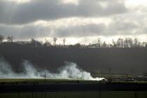 Smoke from a bonfire on a farm, with a treeline and a winter sky, Warwickshire. - John Harris - 16-01-2004