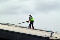 Construction worker with safety harness sealing a roof on a new building. - John Harris - ,2000s,2004,balance balancing,brush,bucket,construction industry,EBF economy,employee,employees,Employment,europeregi,hazard hazardous,health,height,high,job,jobs,LAB LBR work ,LBR,paint,painter,Paint