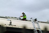 Construction worker with safety harness sealing a roof on a new building. - John Harris - 2000s,2004,balance balancing,brush,bucket,construction industry,EBF economy,employee,employees,Employment,europeregi,hazard hazardous,health,height,high,job,jobs,LAB LBR work ,LBR,paint,painter,Painte