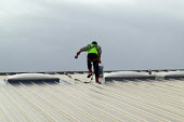 Construction worker with safety harness sealing a roof on a new building. - John Harris - 05-02-2004
