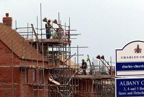 Construction of houses on a new estate on the edge of town. Stratford on Avon. - John Harris - 2000s,2004,bricklayer,bricklayers,bricklaying,builder,builders,building,building site,BUILDINGS,Construction Industry,development,EBF economy,greenbelt,homes,house,house building,housebuilder,housebui