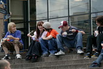 Teenagers sitting around outside McDonalds eating icecream, Birmingham City centre. Saturday. - John Harris - 2000s,2004,adolescence,adolescent,adolescents,Birmingham,boy,boys,child,CHILDHOOD,children,cities,city,eating,female,females,food,FOODS,girl,girls,juvenile,juveniles,kid,kids,LFL leisure,male,McDonald