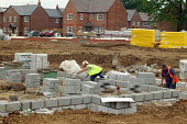 Bricklayer working on a building site constructing new houses, Stratford on Avon, Warwickshire. - John Harris - 2000s,2004,brick,bricklayer,bricklayers,bricklaying,bricks,Brownfield Site,builder,builders,building,building site,BUILDINGS,EBF economy,foundations,houses,LAB LBR work,people,worker,workers,working