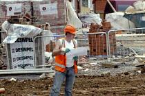 Bricklayer looking at plans. Building site, Stratford Upon Avon, Warwickshire. - John Harris - 2000s,2004,brick,bricklayer,bricklayers,bricklaying,bricks,Brownfield Site,builder,builders,Building,building site,BUILDINGS,Construction Industry,EBF,EBF economy,Economic,Economy,foundations,houses,j