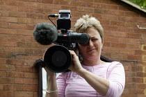 Freelance TV camerwoman filming with digital camera. - John Harris - 2000s,2004,broadcast,broadcasting,cameraman,communicating,communication,digital,filming,Freelance,freelances,job,jobs,LAB LBR work,media,news,people,television,TV,Video,worker,workers,working