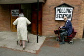 Disabled elderly man and woman arriving at the polls to vote. Amersham, Buckinghamshire - John Harris - 2000s,2004,access,adult,adults,age,ageing population,ARRIVAL,arrivals,arrive,arrived,arrives,arriving,bound,communicating,communication,council,democracy,disabilities,disability,disable,disabled,disab