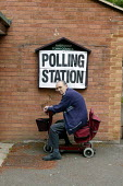 Disabled elderly man arriving at the polls to vote. Amersham, Buckinghamshire - John Harris - 2000s,2004,access,adult,adults,age,ageing population,ARRIVAL,arrivals,arrive,arrived,arrives,arriving,bound,communicating,communication,council,democracy,disabilities,disability,disable,disabled,disab