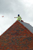 Roofing contractor on the roof of new houses, throwing a tile to the ground below. Stratford upon Avon - John Harris - 2000s,2004,apex,balance,balancing,builder,builders,building site,Construction Industry,contractor,contractors,EBF,EBF economy,Economic,Economy,employee,employees,Employment,hazard,hazardous,hazards,he