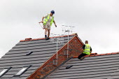 Roofing contractors on the roof of new houses, without harness or hard hat, Stratford upon Avon. - John Harris - 2000s,2004,apex,balance,balancing,builder,builders,building site,Construction Industry,contractor,contractors,EBF,EBF economy,Economic,Economy,employee,employees,Employment,hat,hats,hazard,hazardous,h