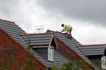 Roofing contractor on the roof of new houses, Stratford upon Avon - John Harris - 2000s,2004,apex,balance,balancing,builder,builders,building site,Construction Industry,contractor,contractors,EBF,EBF economy,Economic,Economy,employee,employees,Employment,hazard,hazardous,hazards,he