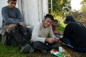 Looking at a photograph. Migrant farm workers have a break from taking down polytunnels used to grow strawberries, Fusion Personnel, Bretforton, Vale of Evesham - John Harris - 09-09-2004