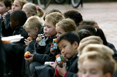 Junior pupils eating a packed lunch, Birmingham. - John Harris - 2000s,2004,boy,boys,child,CHILDHOOD,children,cities,city,diet,diets,drink,drinking,drinks,eating,edu education,food,FOODS,fruit,FRUITS,INDEPENDENT,juice,juvenile,juveniles,kid,kids,male,people,primary