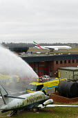 Firefighting appliance extinguishing an aircraft fire on a training exercise, as a passenger jet takes off on the runway behind. Airport Fire Service Birmingham International Airport - John Harris - 31-01-2005