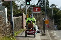 Disabled elderly woman driving her powered wheelchair along the pavement. - John Harris - 28-02-2005