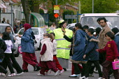 Pupils and parents walking home from school crossing the road Small Heath Birmingham. - John Harris - 05-05-2005