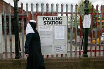 Voter at a polling station in the general election. Small Heath Birmingham. - John Harris - ,2000s,2005,asian,black,BME Black minority ethnic,burka,burkas,burkha,burqa,burqas,cities,city,democracy,dress,election,elections,FEMALE,general,hajib,headscarf,hijab,islam,islamic,local,monotheistic,