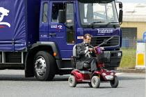 Disabled man driving his motorised wheelchair on the road. - John Harris - 21-06-2005