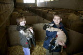Boys in the lambing shed, holding lambs, farm visit, Worcestershire - John Harris - 03-06-2006