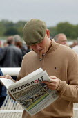Race goer reading the Racing Post. Steeplechase racing at Stratford on Avon racecourse. - John Harris - ,2000s,2006,animal,animals,bet,bets,betting,capitalism,capitalist,chance,cigar,cigars,course,courses,Domesticated Ungulates,ebf economy,equestrian,equine,event,form,gamble,gambler,gamblers,gambling,go