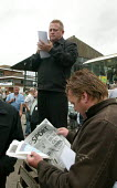 Race goer reading the Racing Post and a tic tac man. Steeplechase racing at Stratford on Avon racecourse. - John Harris - 2000s,2006,accountant,accountants,accounting,animal,animals,bet,bets,betting,bookie,bookies,bookmaker,bookmakers,capitalism,capitalist,chance,course,courses,Domesticated Ungulates,ebf economy,equestri