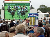 Bookmakers taking bets. Steeplechase racing at Stratford on Avon racecourse. - John Harris - 2000s,2006,accountant,accountants,accounting,animal,animals,bet,bets,betting,board,boards,bookie,bookies,bookmaker,bookmakers,capitalism,capitalist,chance,course,courses,crowd,crowded,display,displays
