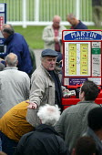 Bookmakers taking bets. Steeplechase racing at Stratford on Avon racecourse. - John Harris - 2000s,2006,accountant,accountants,accounting,animal,animals,bet,bets,betting,board,boards,bookie,bookies,bookmaker,bookmakers,capitalism,capitalist,chance,course,courses,Domesticated Ungulates,ebf eco