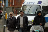 Local residents pass Police outside the Blade cybercafe Sparkhill after raids to foil an alledged terrorist plot. Birmingham. - John Harris - 31-01-2007