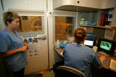 Patient and radiographer at a mobile MRI, magnetic resonance imaging scanner Warwick Hospital. - John Harris - 2000s,2007,and,assessing,ASSESSMENT,bodies,body,care,communicating,communication,COMPUTE,computer,computers,COMPUTING,diagnosis,examination,examining,FEMALE,hea health,health,HEALTH SERVICES,healthcar