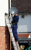 Worker installing a Sky Digital TV satellite dish to the side of a house. - John Harris - 30-04-2007