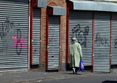 Woman walking past closed shops, Wednesbury, West Midlands. - John Harris - 2000s,2007,anti social behaviour,behavior,behaviour,Boarded Up,cities,city,closed,closing,closure,closures,communities,community,deprivation,EBF Economy,EQUALITY,excluded,exclusion,FEMALE,Graffiti,HAR