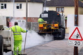 Workers re-surfacing a road in a residential area. Contractor Carillion Highway Maintenance working for Warwickshire County Council applying surface dressing of bitumen and stone chippings to the road... - John Harris - 2000s,2007,applying,communicating,communication,contractor,contractors,Council,Council Services,Council Services,dressed,EBF Economy,gang,heat,highway,hot,LAB LBR Work,Local Authority,machine,machiner
