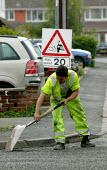 Workers re-surfacing a road in a residential area. Contractor Carillion Highway Maintenance working for Warwickshire County Council applying surface dressing of bitumen and stone chippings to the road... - John Harris - 2000s,2007,aggregate,AGGREGATES,applying,communicating,communication,contractor,contractors,Council,Council Services,Council Services,dressed,EBF Economy,gang,highway,LAB LBR Work,Local Authority,main