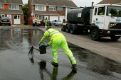 Workers re-surfacing a road in a residential area. Contractor Carillion Highway Maintenance working for Warwickshire County Council applying surface dressing of bitumen and stone chippings to the road... - John Harris - 2000s,2007,applying,contractor,contractors,Council,Council Services,Council Services,dressed,EBF Economy,gang,heat,highway,hot,LAB LBR Work,Local Authority,maintaining,maintenance,male,man,men,operati