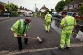 Workers re-surfacing a road in a residential area. Contractor Carillion Highway Maintenance working for Warwickshire County Council applying surface dressing of bitumen and stone chippings to the road... - John Harris - 2000s,2007,applying,contractor,contractors,Council,Council Services,Council Services,dressed,EBF Economy,gang,highway,LAB LBR Work,Local Authority,maintaining,maintenance,male,man,men,older,operative,